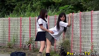 Aasialaiset nuoret ulkona virtsaavat